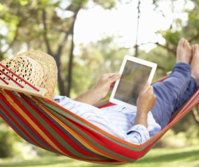 Senior Man Relaxing In Hammock With E-Book